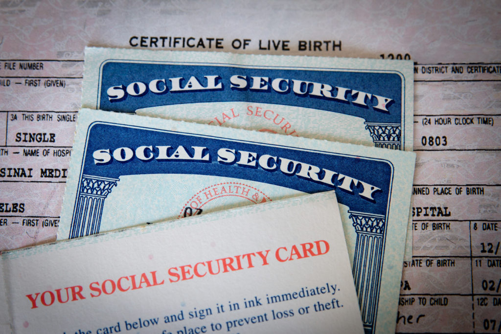 United States Social Security cards with birth certificate background. Concept for life, retirement or death or Government documents and identification.